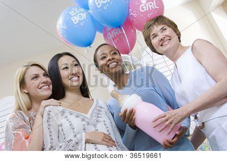 Glückliche schwangere Frau mit Freunden halten große Babyflasche auf Baby-Dusche