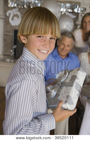 Portrait of teenage boy holding gift for his grandfather with family in the background
