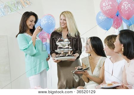 Pregnant woman taking picture of friends having cupcake at a baby shower