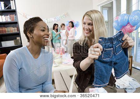 Zwei Freundinnen betrachten Baby-Dusche-Geschenk mit Frauen im Hintergrund