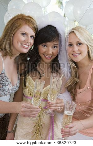Portrait of happy three female friends holding champagne flute