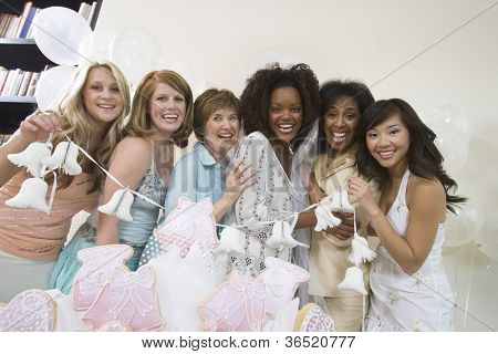 Portrait of female group holding wedding bells at hen party