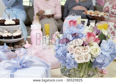 Bouquet and gifts on table with women in background at a baby shower