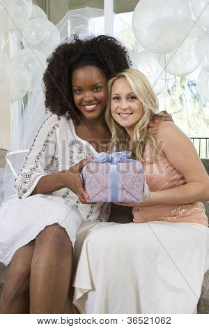 Portrait of happy female friends holding gift at hen party