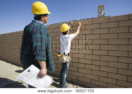 Two male architects inspecting brick wall at construction site