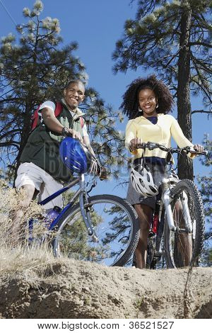 Low angle view of an African American couple standing with bicycles