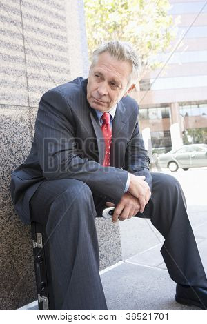 Senior businessman sitting on his briefcase
