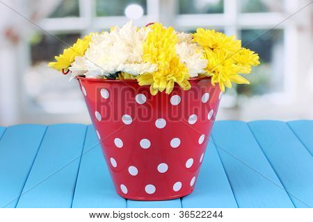 Red pail of peas with flowers on blue wooden table on window background