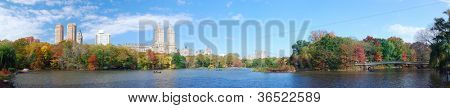 New York City Central Park panorama view in Autumn with Manhattan skyscrapers and colorful trees with Rainbow Bridge over lake with reflection.