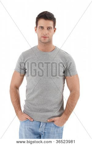Summer portrait of handsome college student guy, standing with hands in pocket, cutout on white.