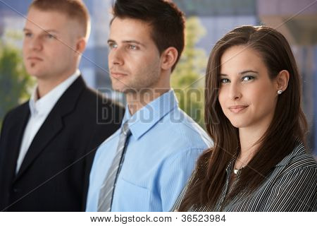 Portrait of smiling businesswoman standing outside of office with colleagues, looking at camera.