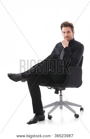 Confident handsome businessman sitting on chair, smiling.