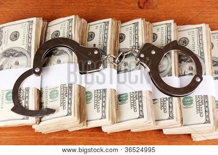 Handcuffs on the packs of dollars on wooden table close-up