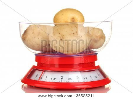 fresh potatoes in a kitchen scales isolated on white