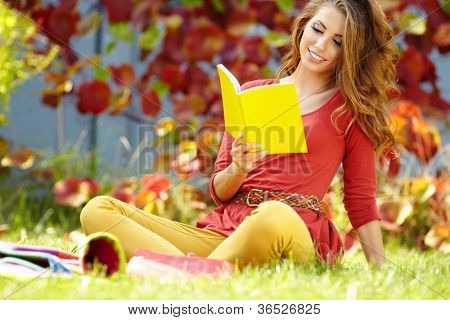 Portrait of beautiful young brunette girl reading a book in the park at fall.