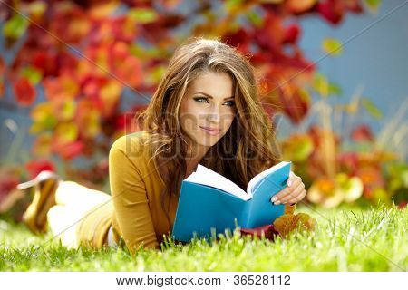 Young  woman lies on green grass and reads book against autumn  park.