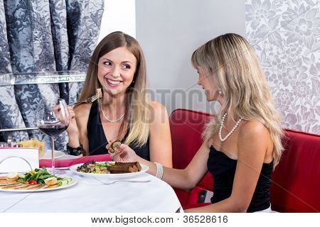 Smiling girls having dinner at the restaurant