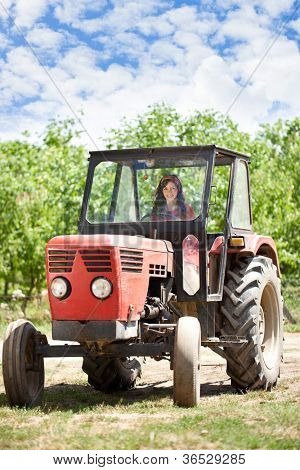 Young country girl driving tractor