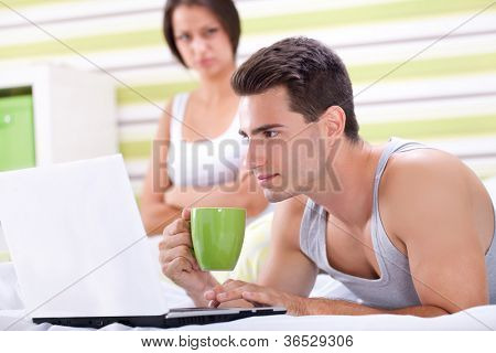 Man at computer, women upset and angry looking at man. Young modern interracial couple in bed.