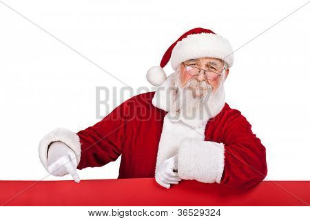 Santa Claus  leaning on big red banner and pointing in it, isolated on white background