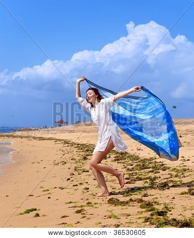 The attractive woman with a beach scarf in hands