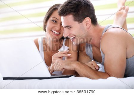 smiling couple shopping on line with credit card from bedroom