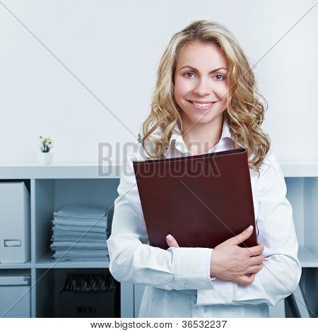 Happy blonde woman with CV and resume in the office
