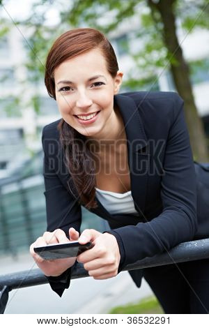 Smiling happy business woman in the city with a smartphone