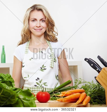 Attractive smiling woman standing in kitchen with vegetables behind chopping board