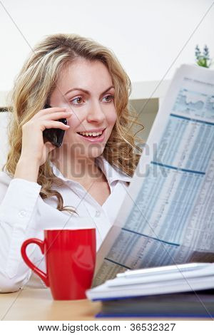 Business woman in office reading a newspaper and making a call with her smartphone