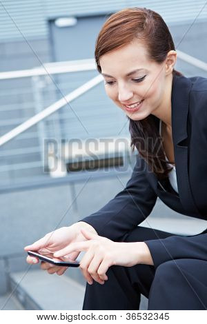 Young business woman sitting on stairs using a smartphone