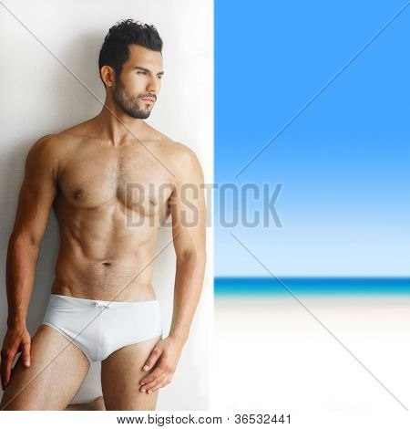 Sexy portrait of a very muscular shirtless male model in underwear against white wall in sensual pose with tropical paradise in background