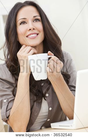 A beautiful young  woman or girl with a wonderful enigmatic smile using laptop computer or pc while drinking tea or coffee from a white cup at home