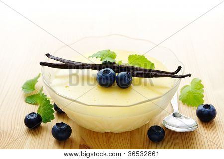 Bowl of homemade vanilla pudding decorated with vanilla beans and blueberries
