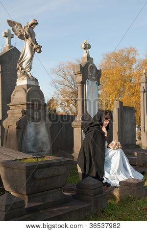 Junge Witwe in Victorian Kleid sitzt auf einem Grabstein