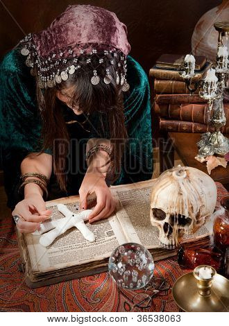 Voodoo gypsy putting needles in a doll casting a spell or curse on it (the book is 300 years old, no copyright problems)