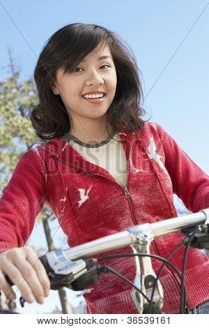 Young cheerful Asian woman riding bicycle against clear sky