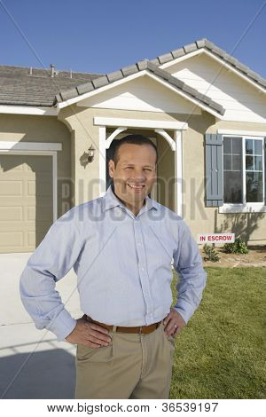Portrait of happy middle aged man with hands on hips in front of new house