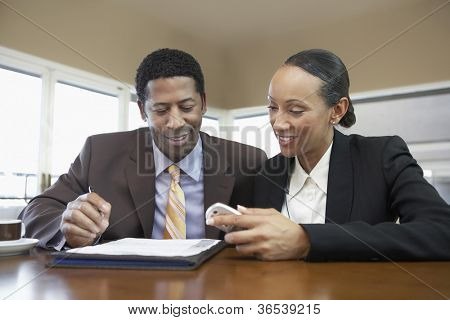 Happy business colleagues reading document at office