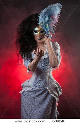 Beautiful Halloween vampire woman aristocrat with venetian mask