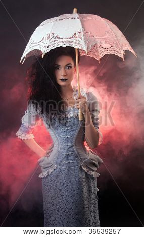 Surprised beautiful Halloween vampire woman aristocrat with lace-parasol