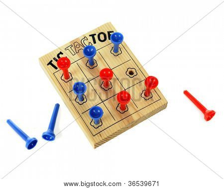 Close up image of a wooden tic-tac-toe game using plastic pegs.  Taken from above. Red wins!  On a white background.