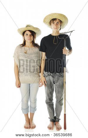 "A teen ""country bumpkin"" couple standing stiff and expressionless, barefoot in jeans and straw hats.  The boy holds a garden rake.  On a white background."