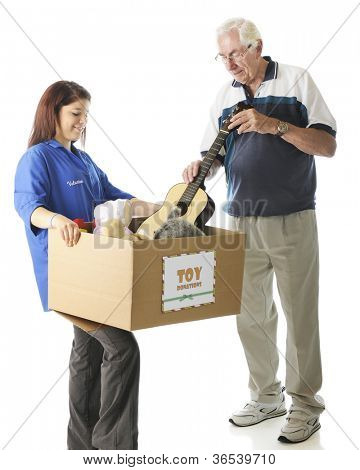 """A young teen holding a large box with a holiday """"Toy Donations"""" sign as an elderly man is donating a toy guitar.  Focus on girl,  On a white background."""