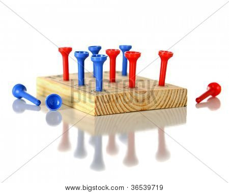 Closeup view of a wooden block game with red and blue plastic pegs.  On a white background.  Reflected off the white surface.