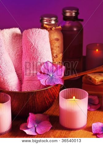 Photo of bath accessories on wooden table over purple background, picture of spa candles, image of alternative treatment items, day spa concept, pink still life, health and beauty care
