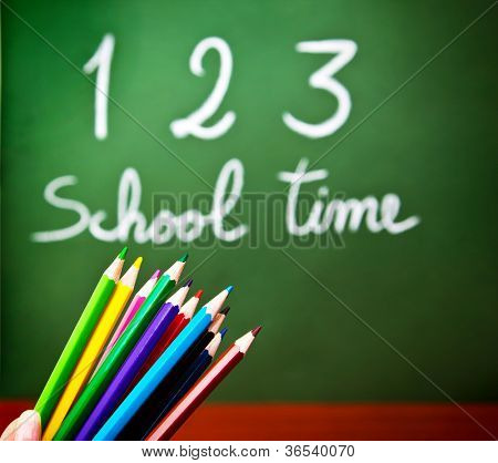 """Image of colorful pencils and green chalkboard with selective focus, multi colors crayons in preschool, handwriting phrase """"school time"""" on blackboard in classroom, education and knowledge concept"""