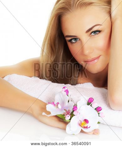 Photo of beautiful woman with pink orchid isolated on white background, blonde pretty girl sitting and holding fresh flower in hand, young lady closeup portrait, day spa, beauty and health treatment