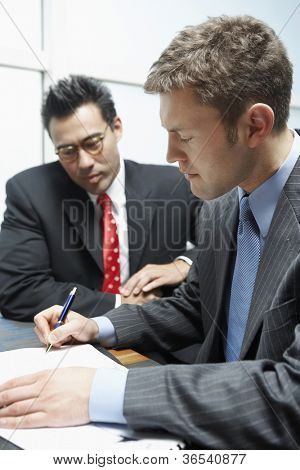 Businessman signing a contract with business partner in the background