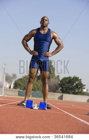 Full length of African American female athlete at starting block on race track
